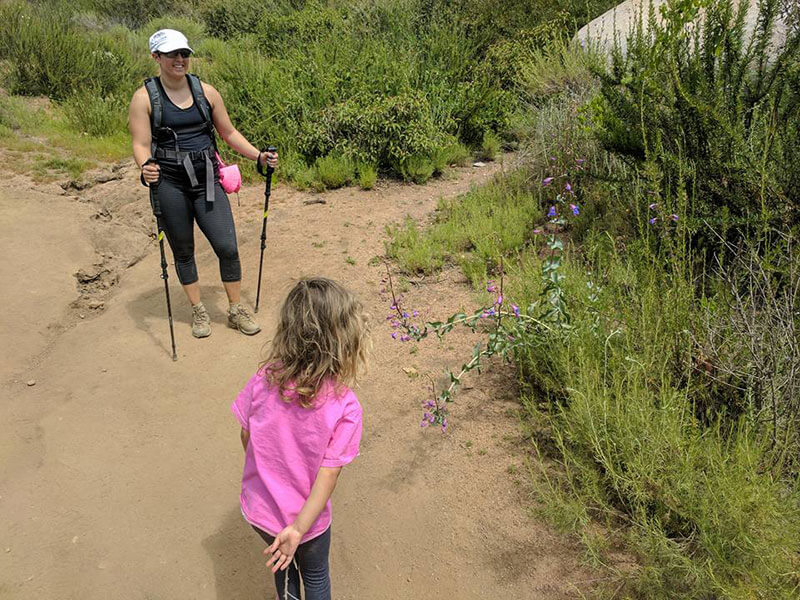 Amanda hiking on a trail with daughter